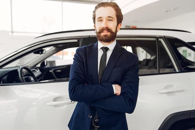 Hübscher und eleganter mann in einem autosalon Kostenlose Fotos