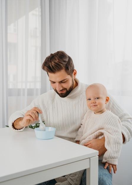 Hübscher vater, der sein baby füttert Premium Fotos