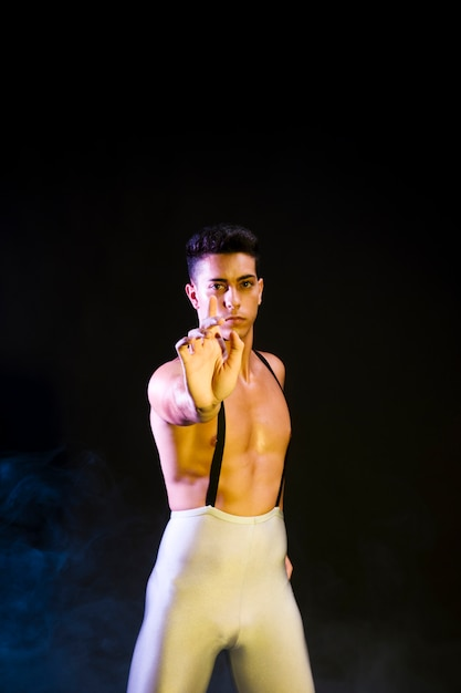 Hübscher zeitgenössischer tänzer, der im scheinwerferlicht durchführt Kostenlose Fotos