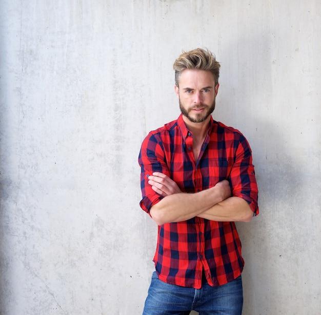 Hübscher zufälliger mann mit dem bart, der mit den armen gekreuzt aufwirft Premium Fotos
