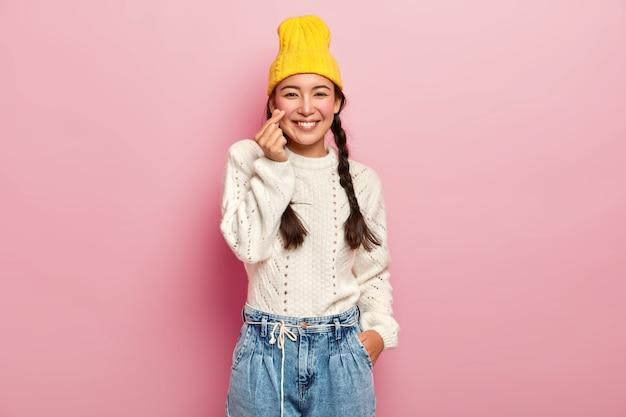Hübsches asiatisches mädchen hält finger in herzsymbol gefaltet, zeigt koreanisches liebeszeichen, trägt stilvollen gelben hut, weißen pullover und jeans, hat dunkles haar in zwei zöpfen gekämmt, posiert gegen rosa wand Kostenlose Fotos