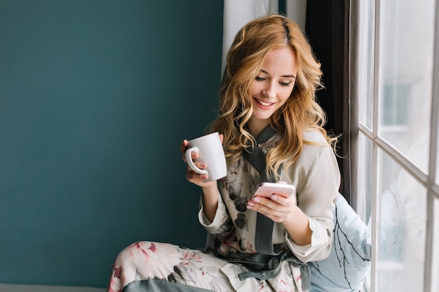 Hübsches blondes mädchen, das auf fensterbank mit tasse kaffee, tee und smartphone in den händen sitzt. sie hat langes blondes, welliges haar, lächelt und schaut auf ihr handy. trage einen schönen seidenpyjama. Kostenlose Fotos