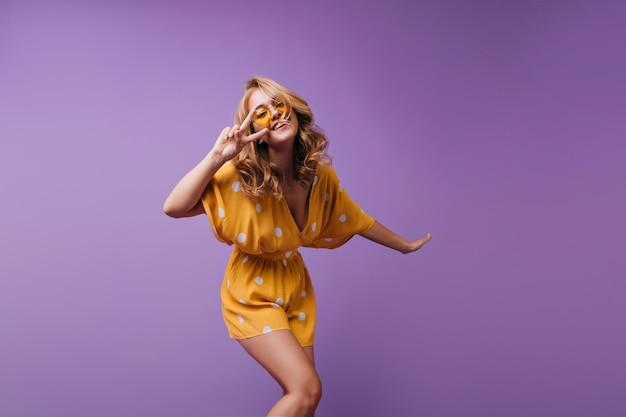 Hübsches blondes mädchen mit gebräunter haut, lustiges tanzen und lachen. porträt der freudigen europäischen dame, die positive gefühle ausdrückt. Kostenlose Fotos