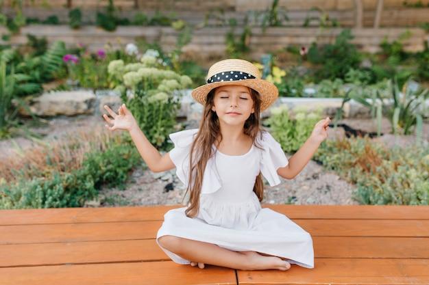 Hübsches brünettes weibliches kind im strohhut, das nahe blumenbeet in lotushaltung mit geschlossenen augen sitzt. kleines mädchen im weißen kleid, das yoga im garten tut Kostenlose Fotos