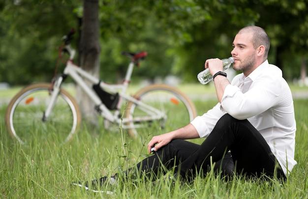 Hübsches erwachsenes männliches trinkwasser im freien Premium Fotos