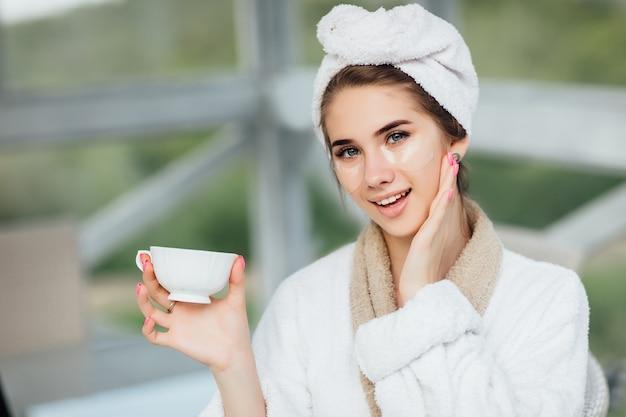 Hübsches gesicht. attraktives, lächelndes mädchen in der weißen robe, sitzend an der hotelterrasse und tasse kaffee oder tee halten. make-up-konzept. Premium Fotos