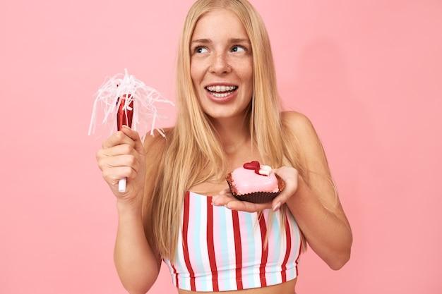 Hübsches jugendlich mädchen mit glattem haar und zahnspangen auf ihren zähnen, die geburtstag feiern, isoliert mit partygebläse und süßem dessert posieren, wunsch machen, verträumten freudigen gesichtsausdruck haben Kostenlose Fotos