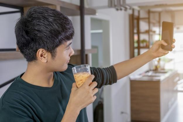 Hübsches junger mann selfie glücklich in der küche Premium Fotos