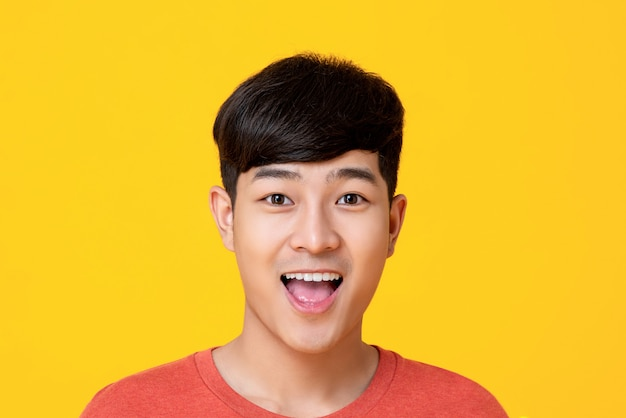 Hübsches junges asiatisches manngesicht, das mit dem mund offen lächelt Premium Fotos