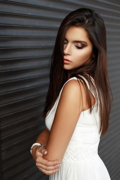 Hübsches junges mädchen mit make-up im weißen kleid nahe dunkler metallwand Premium Fotos