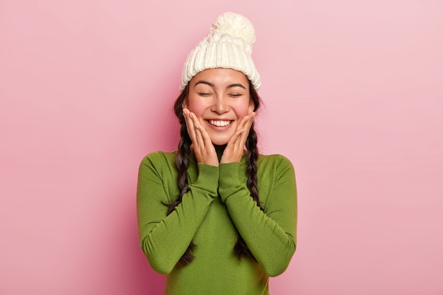 Hübsches junges weibliches model fühlt sich wohl, berührt die wangen mit beiden handflächen, trägt einen warmweißen winterhut und einen lässigen grünen rollkragenpullover, hat ein breites strahlendes lächeln und posiert über einer rosa wand Kostenlose Fotos