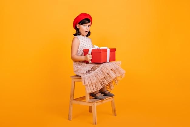 Hübsches kleines mädchen im kleid, das auf stuhl sitzt und große geschenkbox hält. französisches kind mit geburtstagsgeschenk. Kostenlose Fotos
