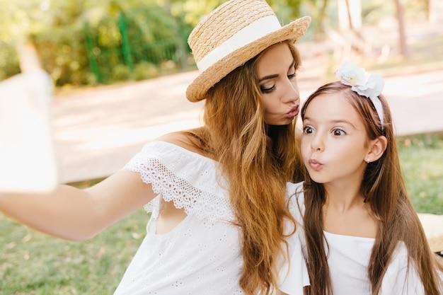 Hübsches kleines mädchen mit großen braunen augen, die mit überraschtem gesichtsausdruck aufwerfen, während ihre mutter smartphone hält. stilvolle frau küsst tochter in der stirn und macht selfie. Kostenlose Fotos