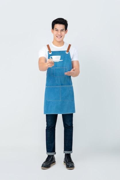 Hübsches lächelndes serviceorientiertes asiatisches mann barista, das einen tasse kaffee dient Premium Fotos