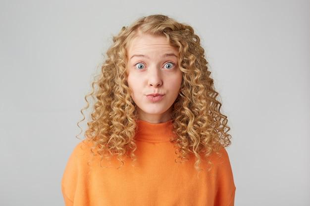 Hübsches lockiges blondes mädchen, das vorne mit geknallten augen steht, die auf weißer wand lokalisiert werden Kostenlose Fotos