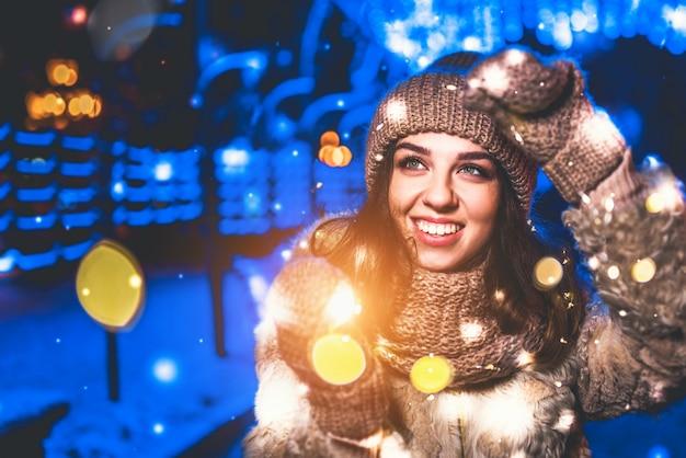 Hübsches mädchen auf der straße mit weihnachtslichtern herum Premium Fotos