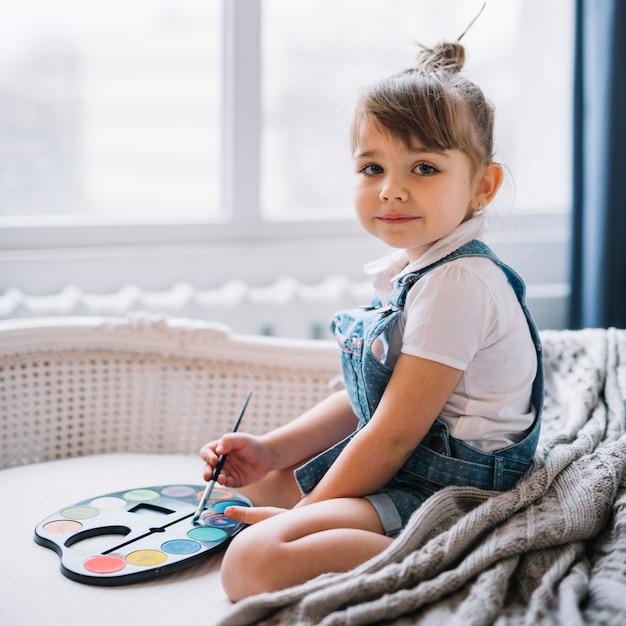 Hübsches mädchen, das auf sofa mit aquarellpalette sitzt Kostenlose Fotos