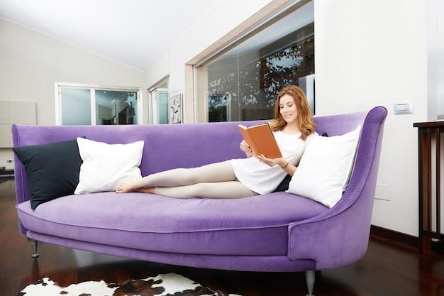 Hübsches mädchen, das ein buch auf purpurrotem sofa liest Premium Fotos