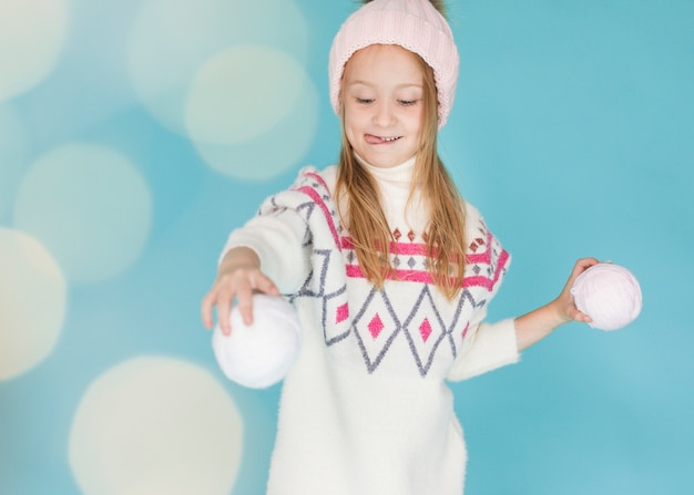 Hübsches mädchen, das mit schneebällen spielt Kostenlose Fotos