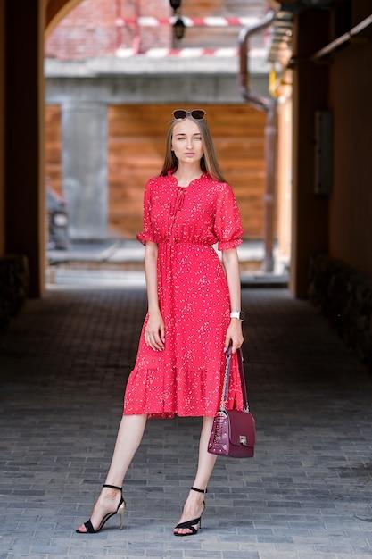 Hübsches mädchen im roten kleid gehend auf die straße in der alten stadt Premium Fotos