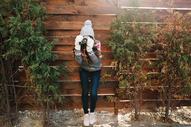 Hübsches mädchen in voller länge mit langen haaren in strickmütze, handschuhen und jeans, die foto auf kamera auf grünen zweigen der hölzernen einfassung machen. Kostenlose Fotos