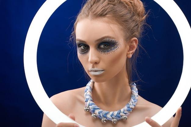 Hübsches mädchen mit dem bunten make-up an der dunklen wand Kostenlose Fotos