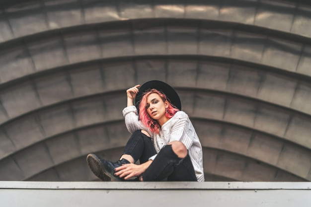 Hübsches mädchen mit dem roten haar und hut, die im städtischen platz aufwerfen. Premium Fotos