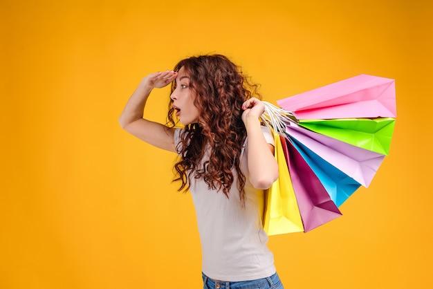 Hübsches mädchen mit den einkaufstaschen, die nach den geschäften lokalisiert über gelb suchen und suchen Premium Fotos