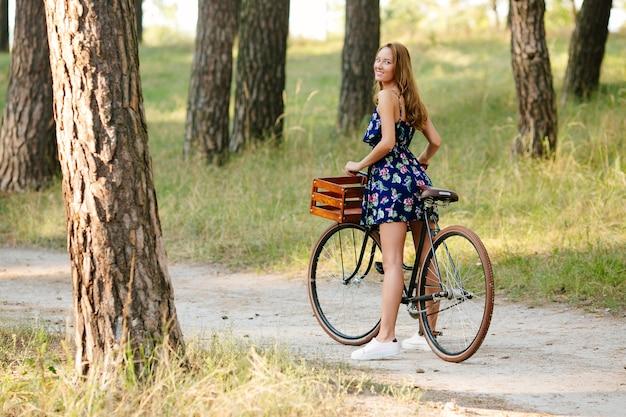 Hübsches mädchen mit einem fahrrad im wald. Kostenlose Fotos