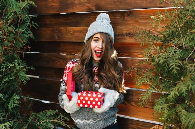 Hübsches mädchen mit langen haaren in der winterkleidung auf holz. sie hält weihnachtsgeschenk in handschuhen und sieht erstaunt aus. Kostenlose Fotos