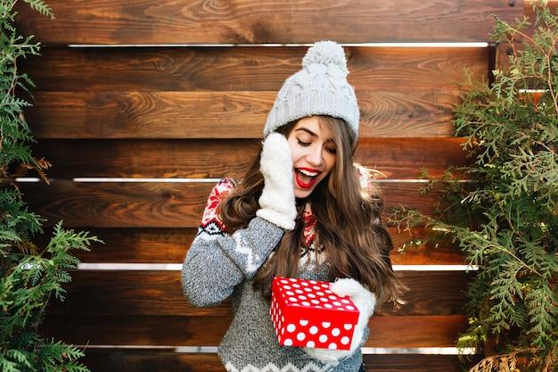 Hübsches mädchen mit langen haaren in der winterkleidung auf holz. sie hält weihnachtsgeschenk und sieht überrascht aus. Kostenlose Fotos