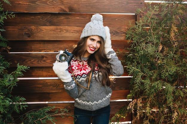 Hübsches mädchen mit langen haaren in strickmütze und handschuhen auf holz. sie trägt einen pullover, hält die kamera und lächelt. Kostenlose Fotos