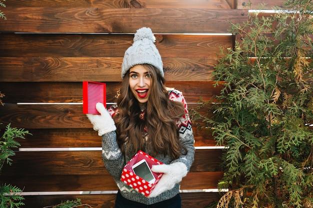 Hübsches mädchen mit langen haaren in strickmütze und warmem pullover auf holz. sie hält weihnachtsgeschenk mit telefon in handschuhen und sieht erstaunt aus. Kostenlose Fotos