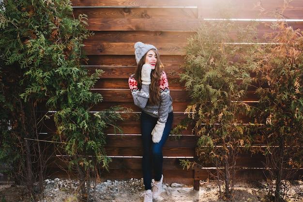 Hübsches mädchen mit langen haaren in strickmütze und warmen handschuhen auf holz. sie lächelt zur seite. Kostenlose Fotos