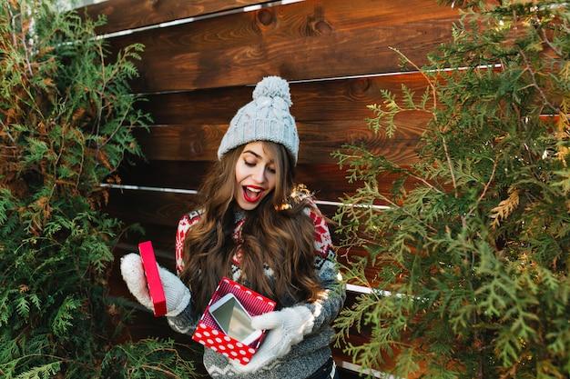 Hübsches mädchen mit langen haaren in winterkleidung auf grünen blättern der hölzernen außeneinfassung. sie hält weihnachtsgeschenk in handschuhen und sieht erstaunt aus. Kostenlose Fotos