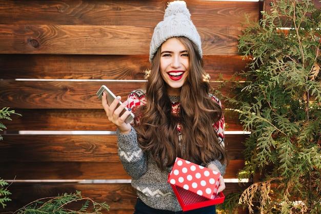 Hübsches mädchen mit langen haaren und roten lippen mit weihnachtsbox und telefon auf holz. sie trägt warme winterkleidung und lächelt. Kostenlose Fotos