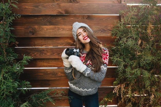 Hübsches mädchen mit langen haaren und schneeweißem lächeln in strickmütze und handschuhen auf holz im freien. sie trägt einen pullover, hält die kamera und lächelt. Kostenlose Fotos