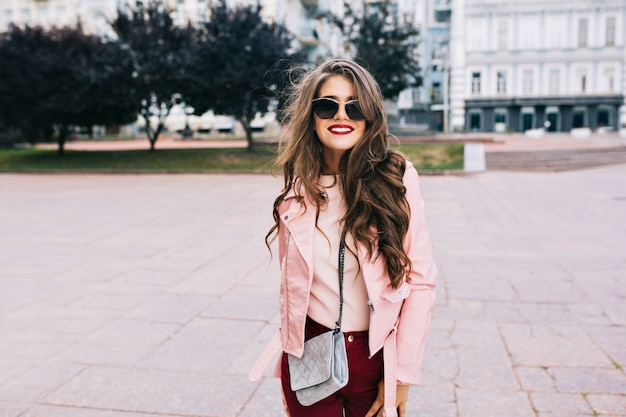 Hübsches mädchen mit langer frisur in der sonnenbrille geht in stadt. sie trägt weinige hosen, eine rosa jacke und lächelt. Kostenlose Fotos