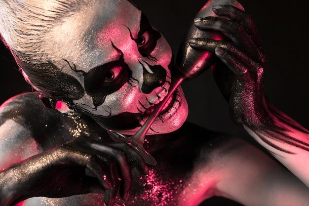 Hübsches mädchen mit skelett make-up hält glas Premium Fotos