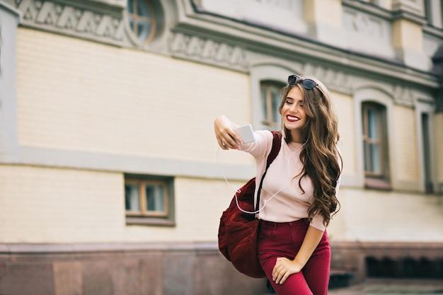Hübsches mädchen mit weinigen lippen und langen haaren macht selfie-porträt in der stadt. sie trägt weinige hosen, tasche. sie sieht aufgeregt aus. Kostenlose Fotos
