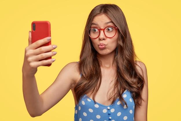 Hübsches mädchen nimmt selfie, schmollt lippen des handys, macht videoanruf, flirtet mit freund, schießt etwas für blog, macht foto von sich selbst, trägt brille, modelle gegen gelbe wand Kostenlose Fotos