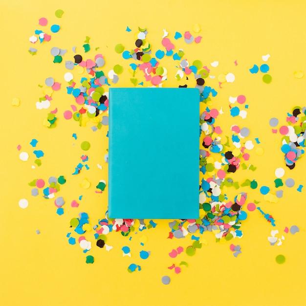 Hübsches notizbuch für spott oben auf gelbem hintergrund mit konfetti herum Kostenlose Fotos