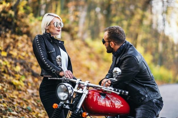 Hübsches paar nahe rotem motorrad auf der straße im wald Premium Fotos