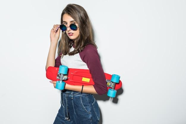 Hübsches skatermädchen in der freizeitkleidung und in der schwarzen sonnenbrille, die rotes skateboard lokalisiert auf weißer wand hält Kostenlose Fotos