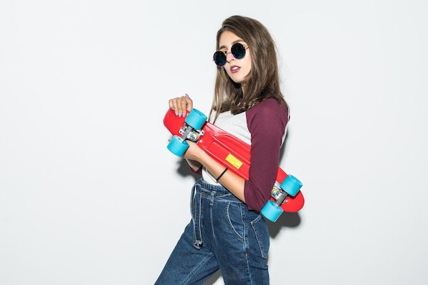 Hübsches skatermädchen in der freizeitkleidung und in der schwarzen sonnenbrille, die rotes skateboard lokalisiert auf weißer wand halten Kostenlose Fotos