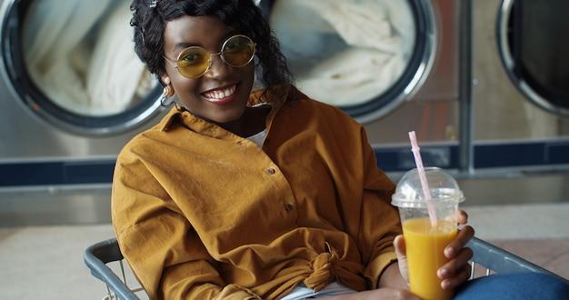 Hübsches und glückliches afroamerikanisches mädchen, das im wagen sitzt und orangensaft mit stroh trinkt, sich ausruht und darauf wartet, dass kleidung gewaschen wird. stilvolle frau nippt getränk im wäscheservice-raum. Premium Fotos