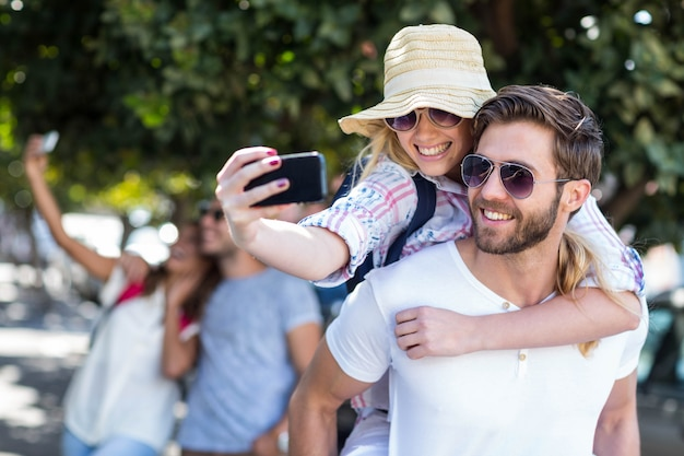 Hüftemann, der seiner freundin doppelpol gibt und selfie auf der straße nimmt Premium Fotos
