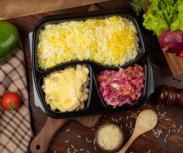 Hühnchen in geschmolzener käsesauce mit reisgarnitur und krautsalat Kostenlose Fotos