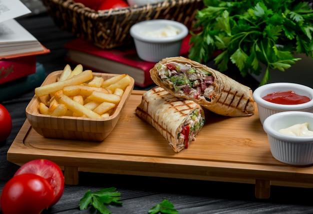 Hühnchen-shaurma, mit fleisch gefüllter lavash und gemüse, serviert mit dip-saucen Kostenlose Fotos