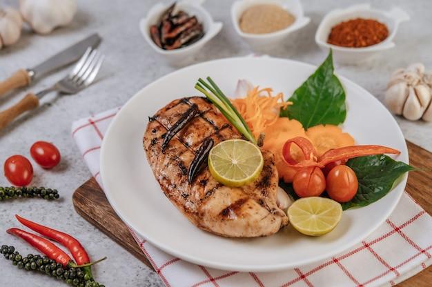 Hühnchensteak mit zitrone, tomate, chili und karotte auf weißem teller. Kostenlose Fotos